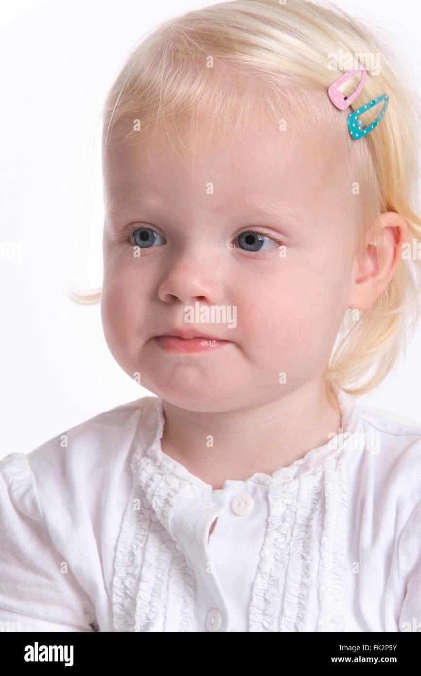Portrait d'un bébé fille blonde avec une expression timide sur fond blanc Photo Stock