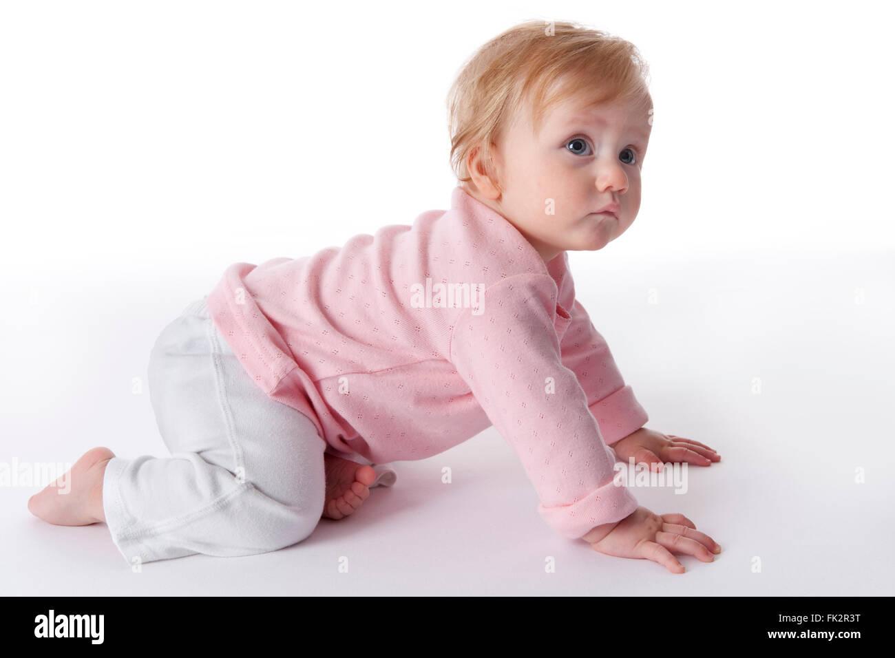 Gril de bébé est de ramper sur le plancher sur fond blanc Photo Stock