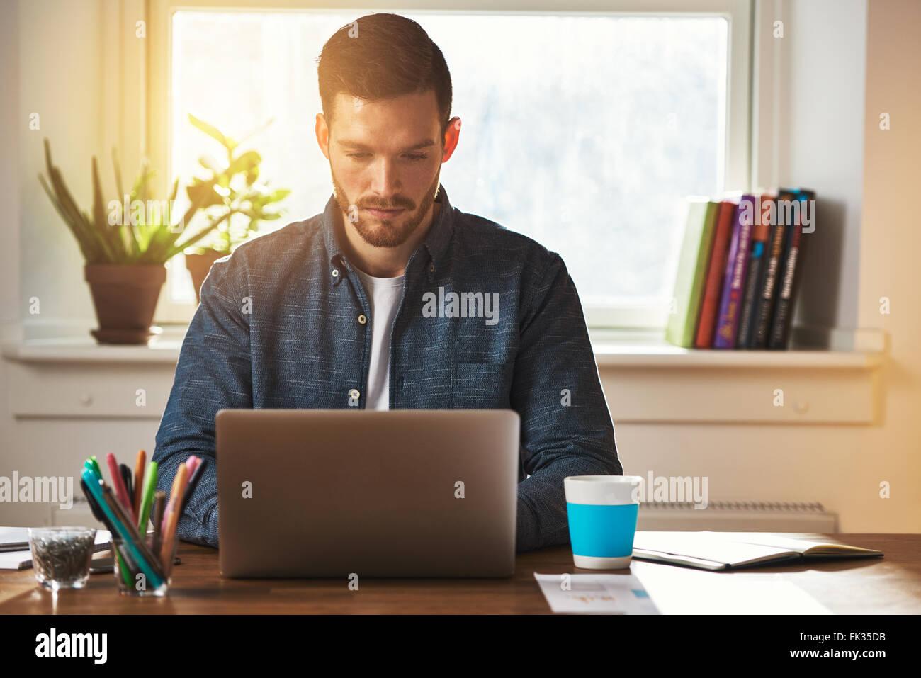 Entrepreneur travaillant sur un ordinateur portable de la saisie ou la navigation sur internet avec une intense Photo Stock