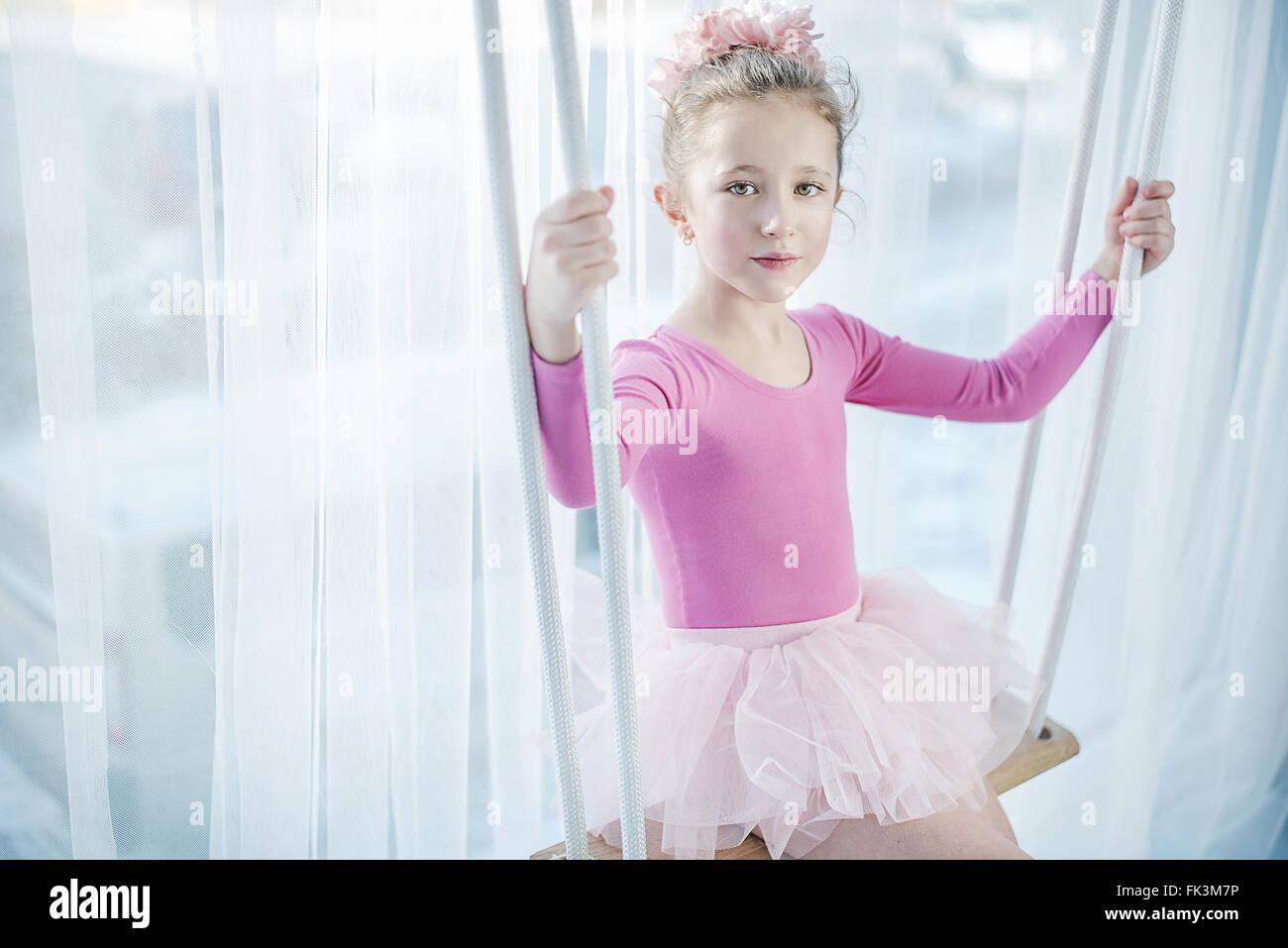 Triste petite fille assise sur une balançoire Photo Stock