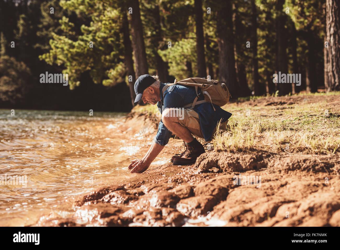 Side portrait of senior male hiker sitting by a lake et mettant les mains dans l'eau. Homme mûr lave-face Photo Stock