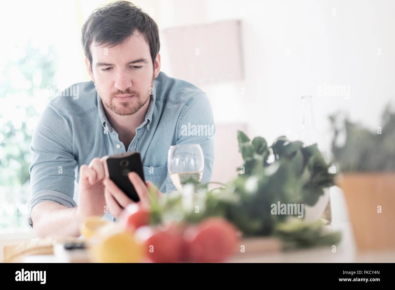 L'homme à l'aide de Phone in kitchen Photo Stock