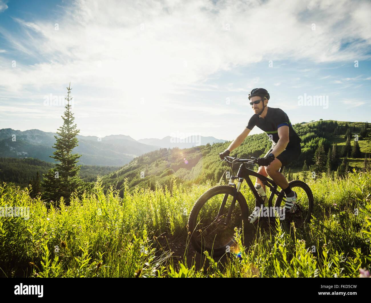 Au cours de l'homme voyage en vélo dans des paysages de montagne Photo Stock