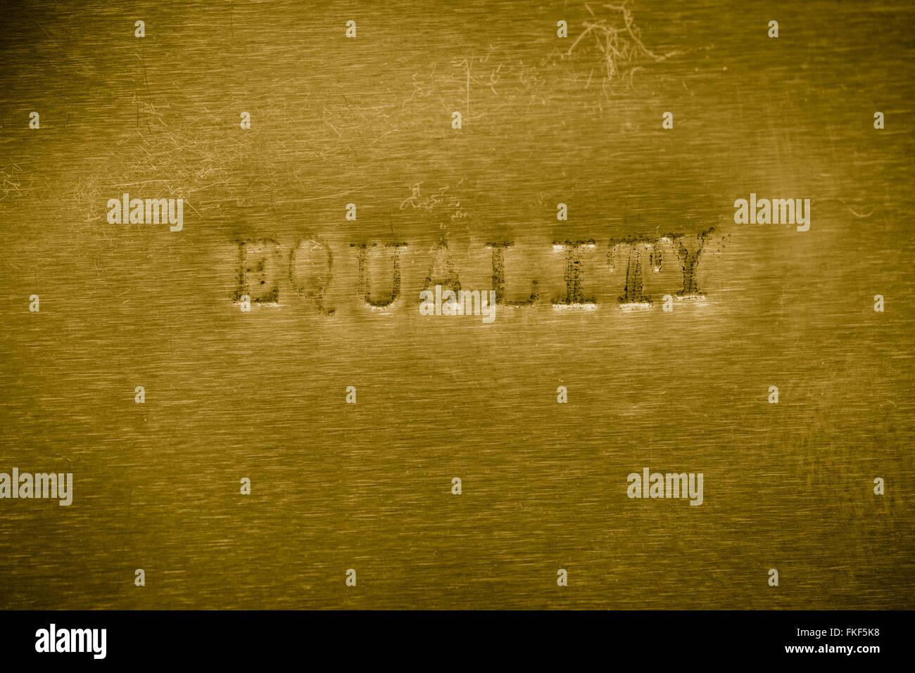 L'égalité de mots imprimés sur texture de fond métallique d'or Photo Stock
