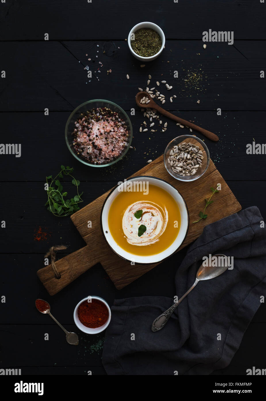 Soupe de potiron à la crème, les graines et les épices dans un bol en métal rustique sur planche Photo Stock