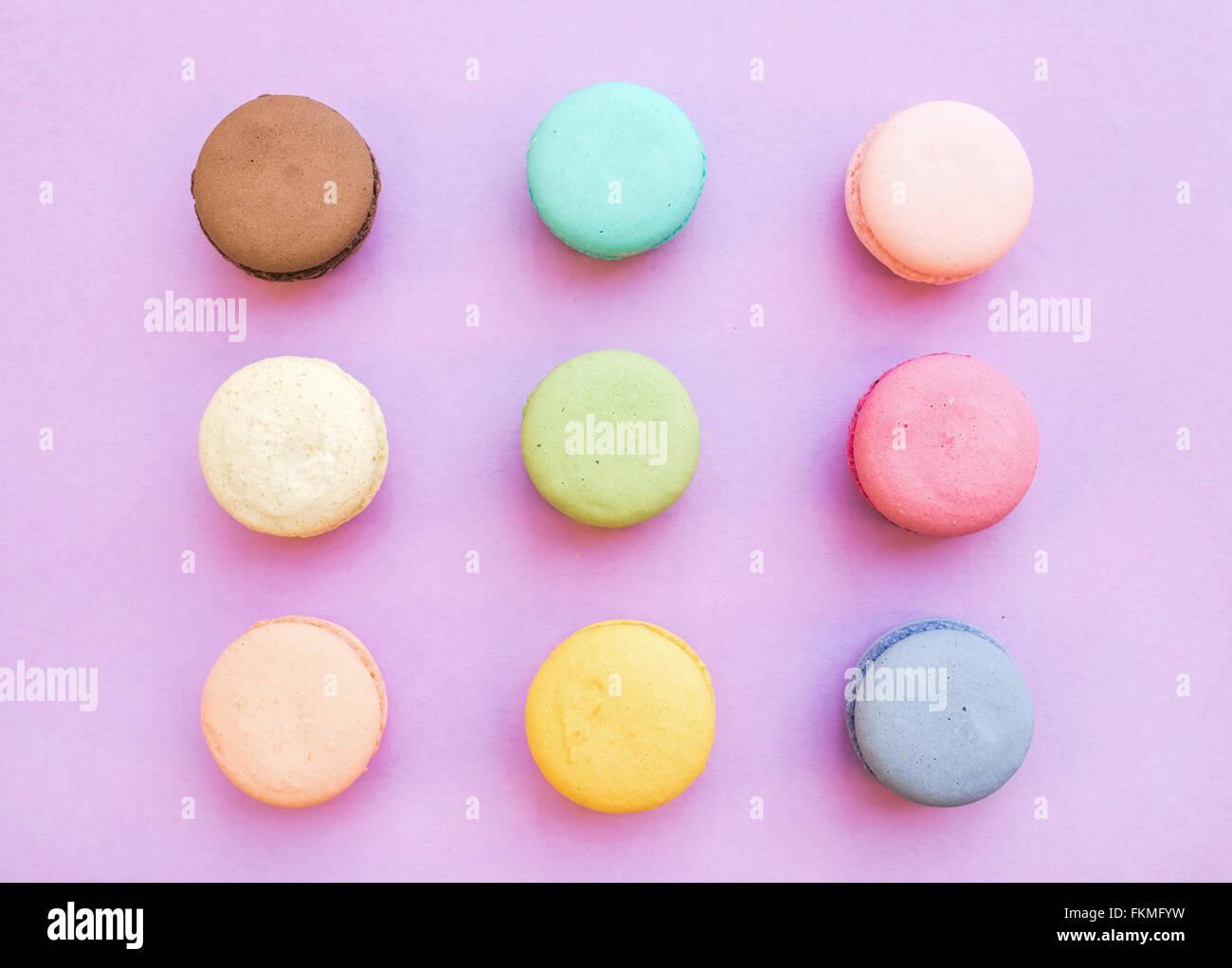 Biscuits macaron français colorés sucré sur fond rose pastel, vue du dessus Photo Stock