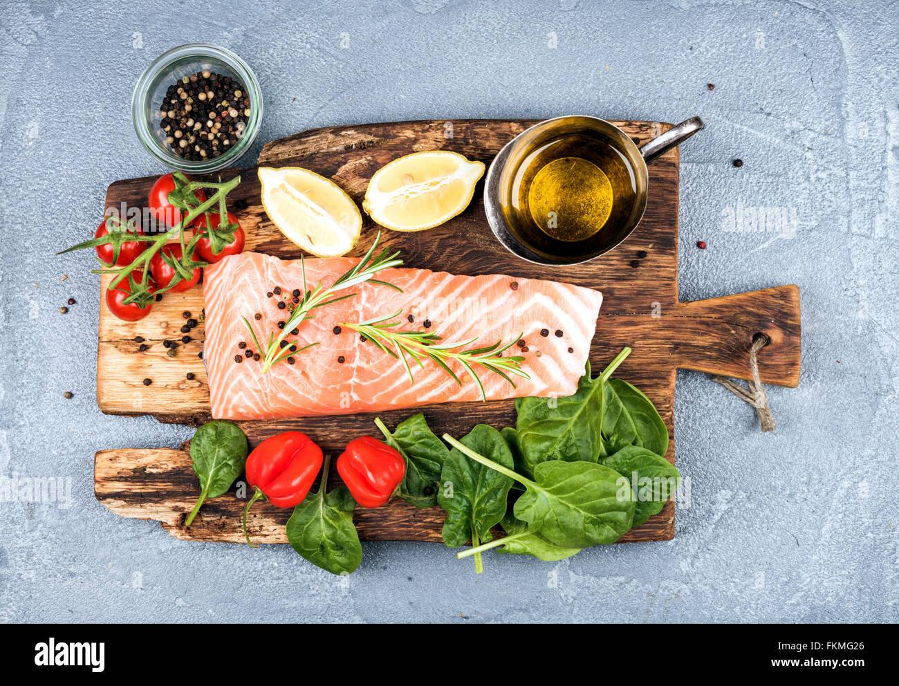 Ingrédients pour cuisiner un dîner sain. Filet de saumon cru, épinards, tomates, huile d'olive, Photo Stock