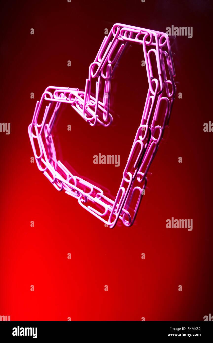 Coeur de trombones sur fond rouge Photo Stock