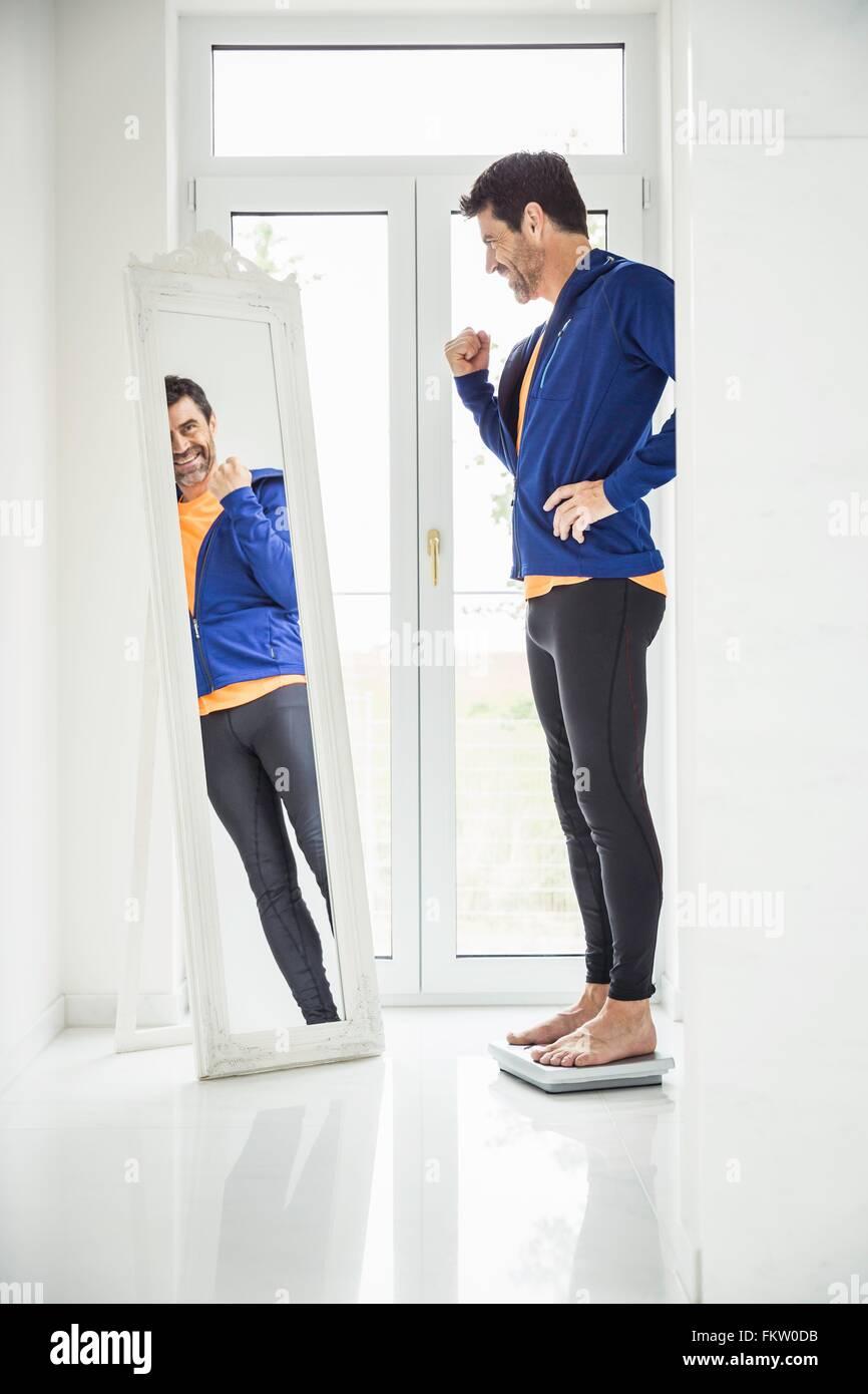 Heureux homme mûr pesant lui-même tout en regardant dans le miroir à la maison Photo Stock