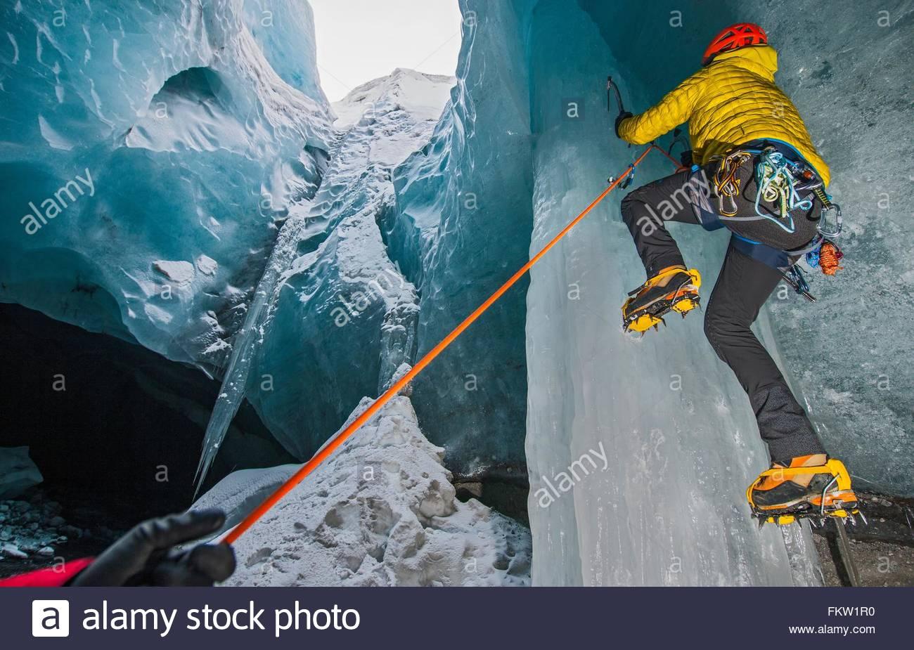 Les glaciéristes grimper au-dessous de la grotte de glace de glacier Gigjokull, Thorsmork, Islande Photo Stock