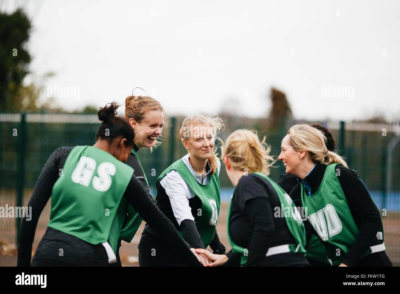 L'équipe de netball féminin se serrer la main sur la cour de netball Photo Stock