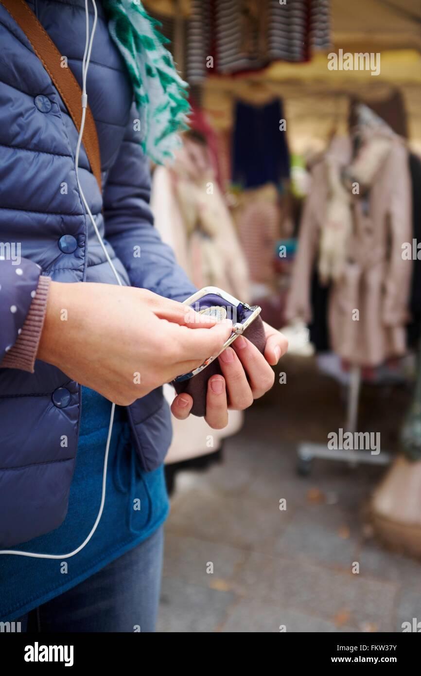 Jeune femme au marché, prendre de l'argent à partir de votre sac à main, mid section Photo Stock