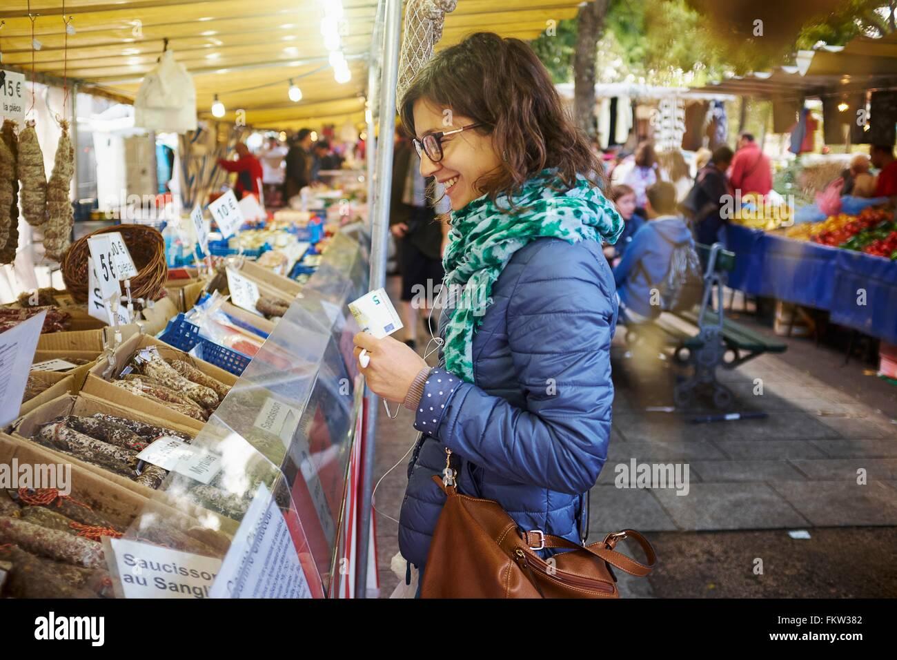 Jeune femme d'acheter des aliments frais à market stall Photo Stock