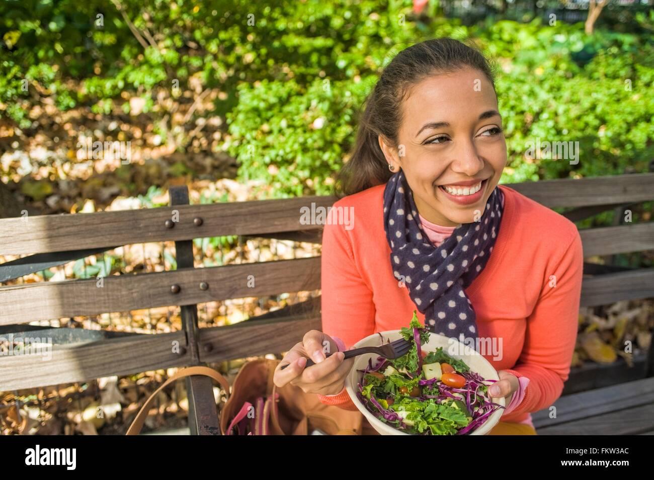 Jeune femme assise sur le banc de parc de manger le déjeuner Photo Stock