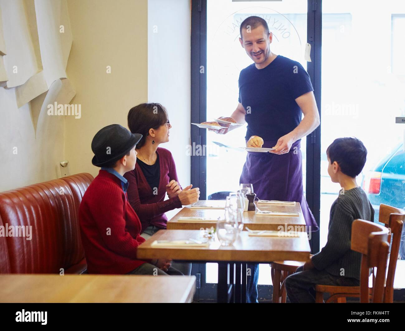 Serveur qui sert le déjeuner dans le restaurant à la femme et fils Photo Stock