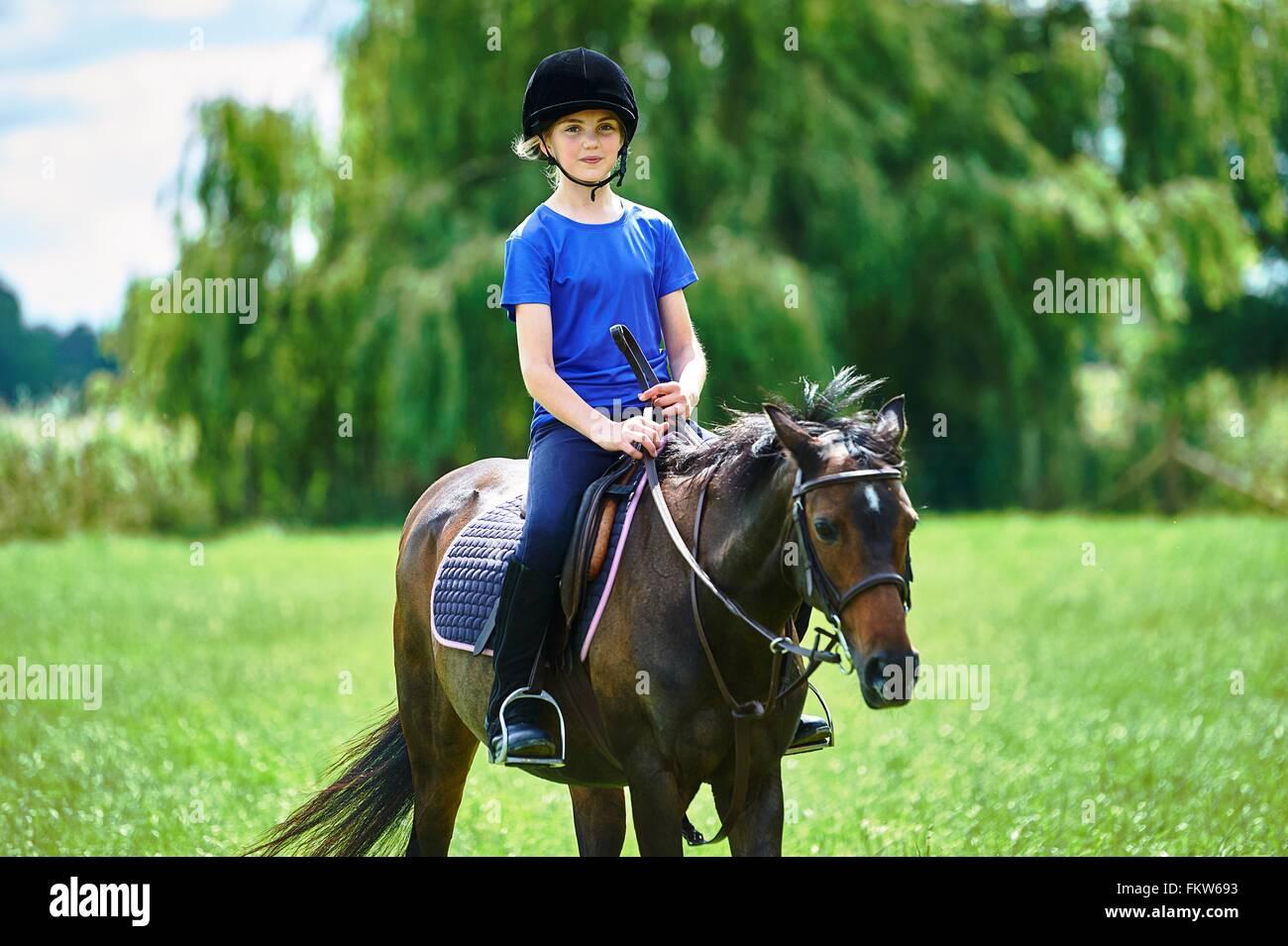 Vue de face de fille à cheval équitation portant hat smiling at camera Photo Stock