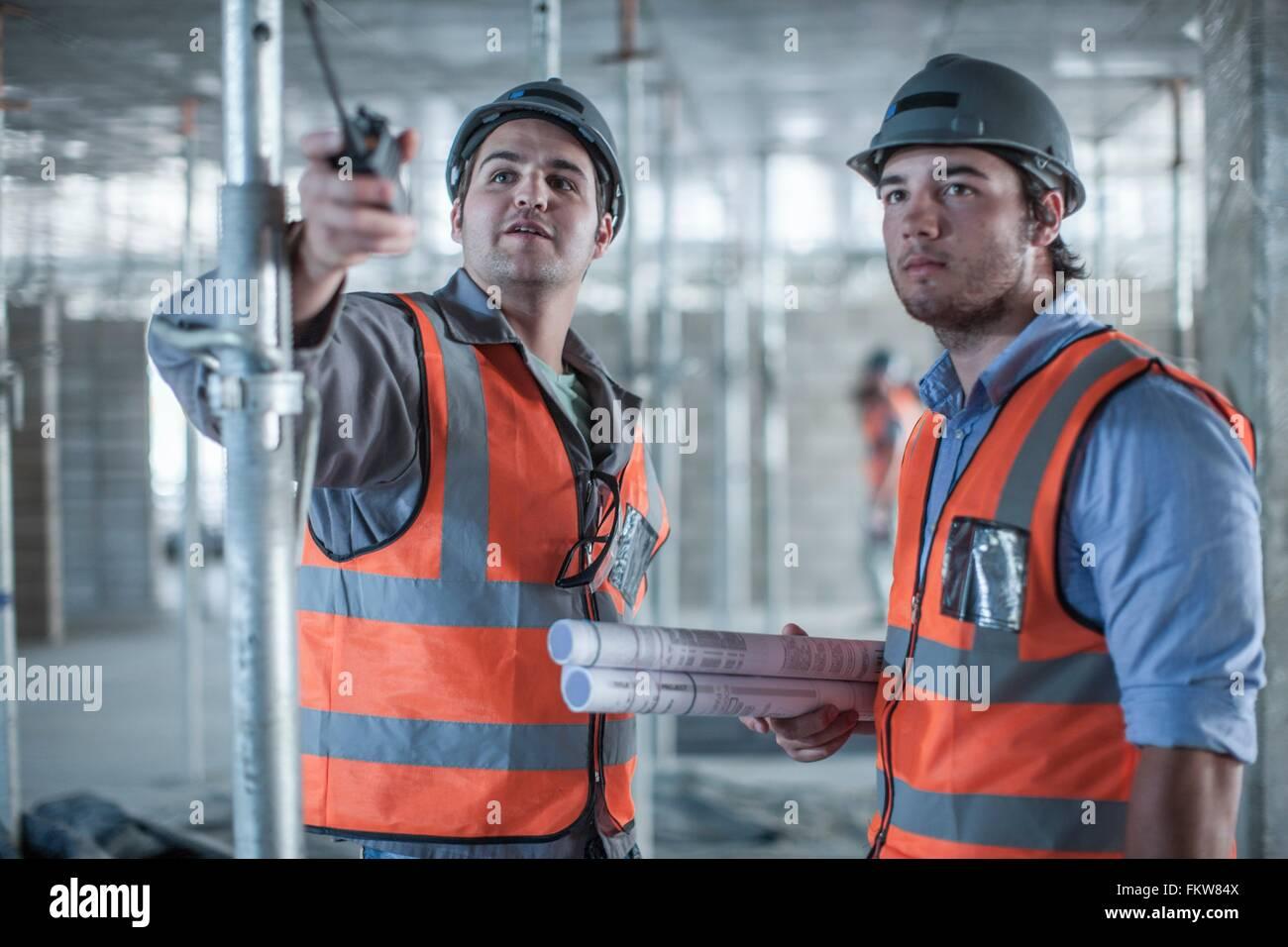 Site manager et builder pointant on construction site Banque D'Images