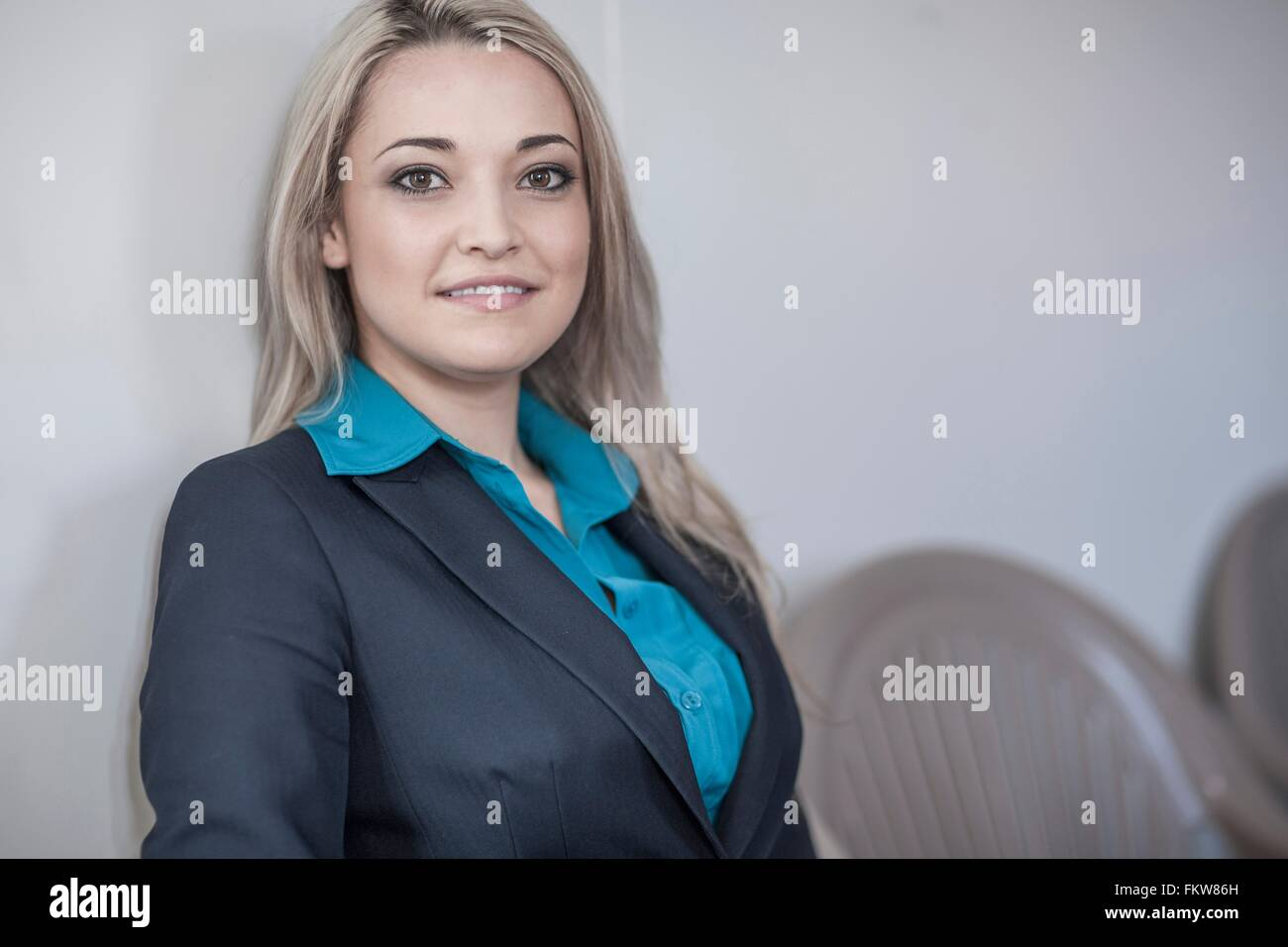 Portrait of young businesswoman avec de longs cheveux blonds sitting in office Photo Stock