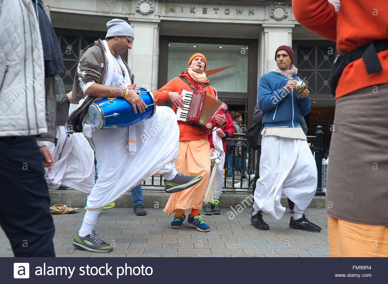 Membres de Hare Krishna danser et chanter parmi les piétons, passage sur Oxford Street au centre de Londres, au Royaume-Uni. Banque D'Images