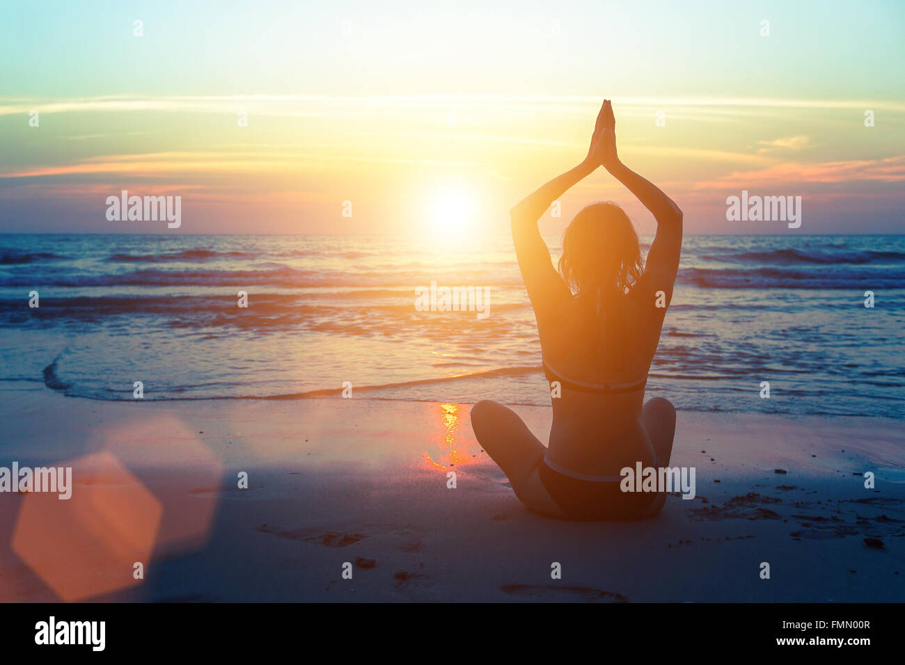 Silhouette of woman practicing yoga on the sea beach. Photo Stock