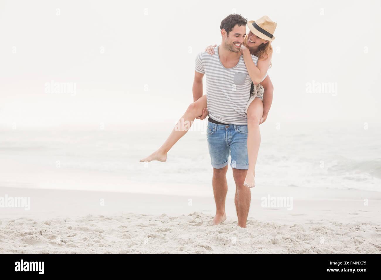 Man giving a piggy retour à la femme sur la plage Photo Stock