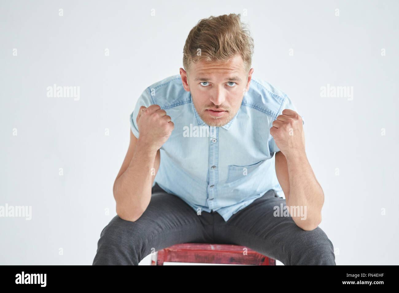 L'homme brutal dans une chemise à manches courtes le fauteuil , les poings serrés , légèrement Photo Stock