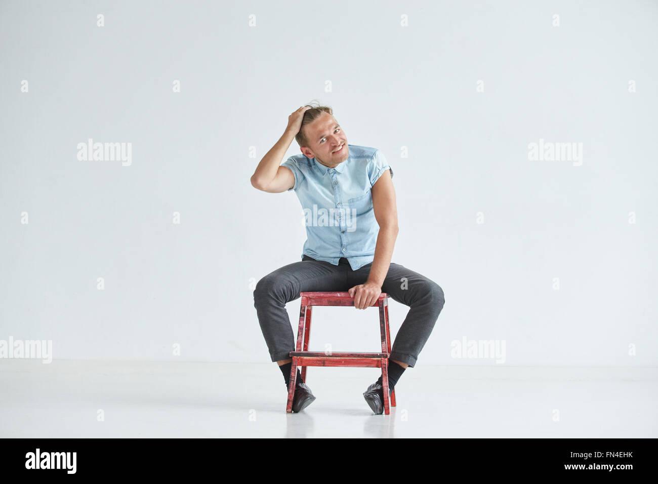 L'homme brutal dans une chemise à manches courtes assis sur chaise rouge , les poings serrés , légèrement Photo Stock