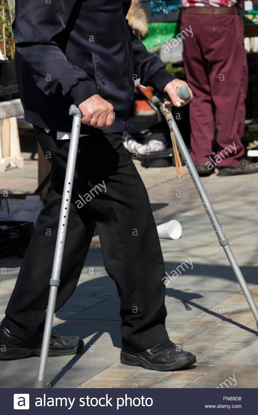 Homme plus âgé marcher avec l'aide de cannes de marche par Salisbury, Wiltshire du marché Photo Stock
