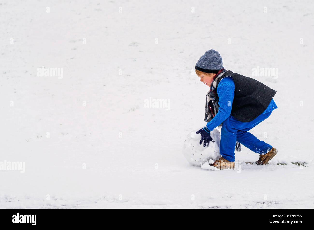 Roulement à billes de neige garçon pour faire un bonhomme de neige Photo Stock