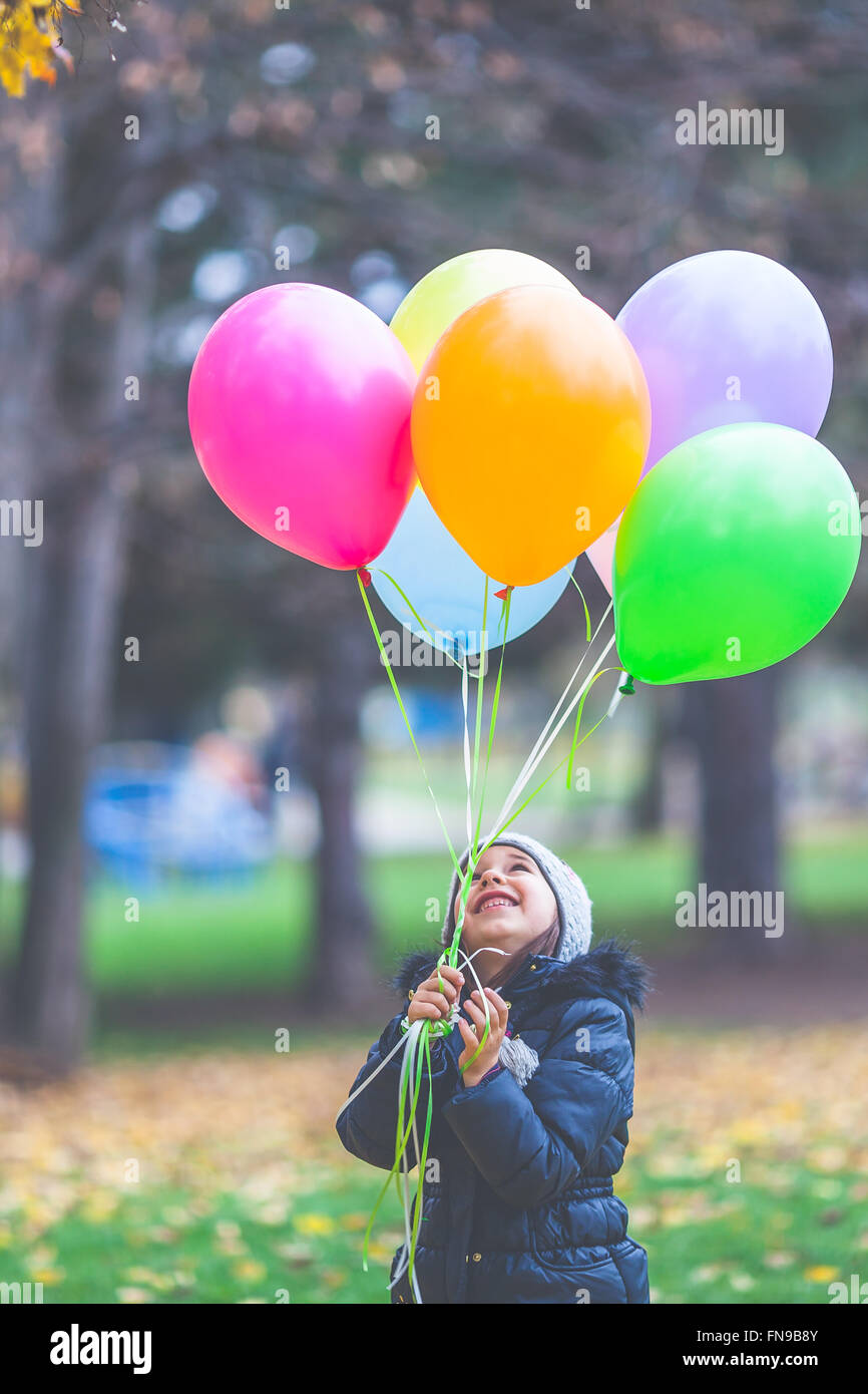 Portrait of a smiling girl holding balloons Banque D'Images