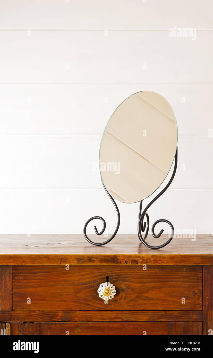Miroir Retro sur table de chevet, arrière-plan blanc mur en bois Photo Stock