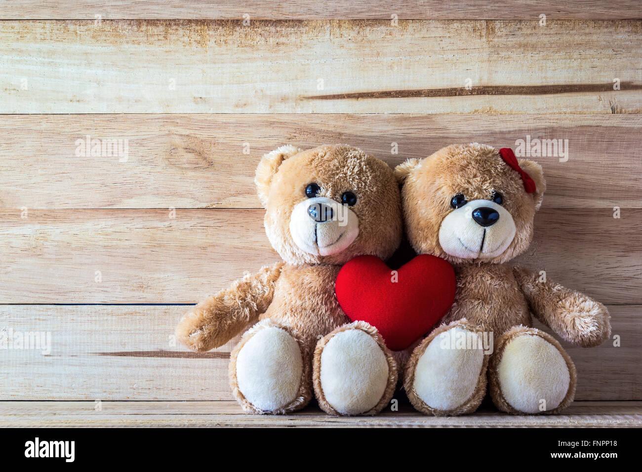 Deux ours en peluche rose avec oreiller en forme de cœur sur planche bois board, Valentine concept Photo Stock