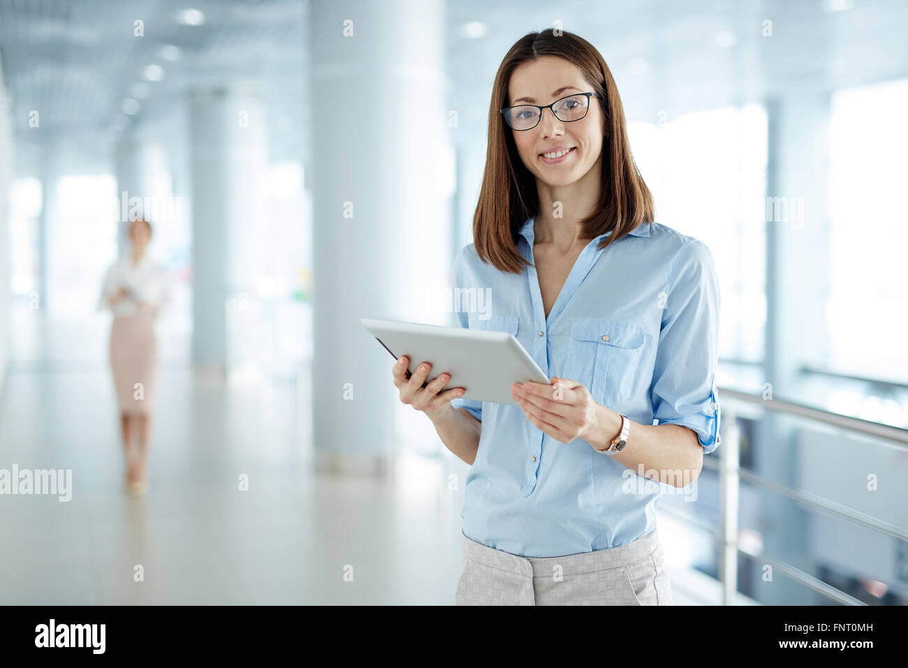 Smiling businesswoman standing avec surface tactile at office Photo Stock