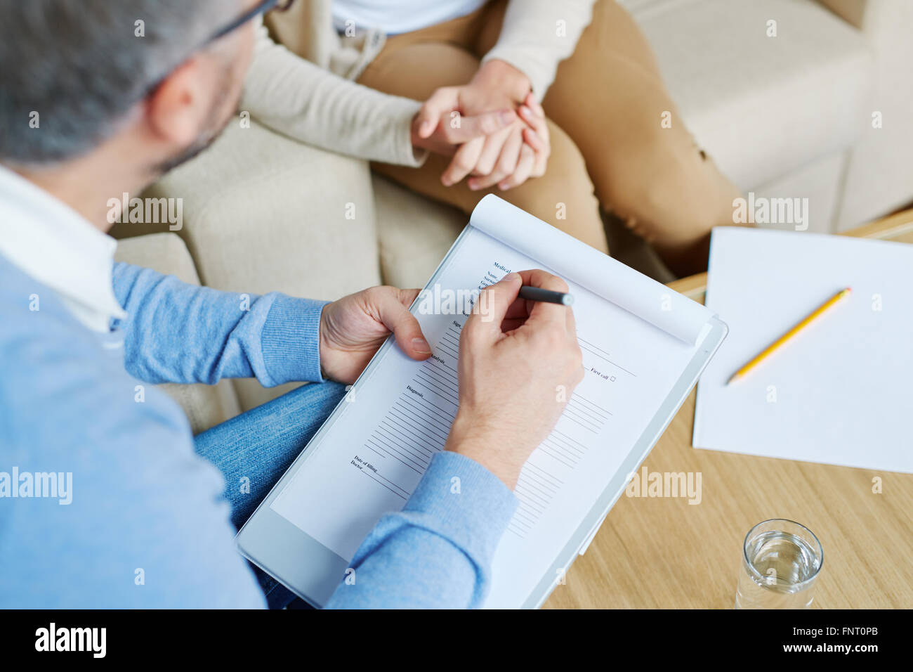 Parler à un psychologue femme appuyée au bureau Photo Stock
