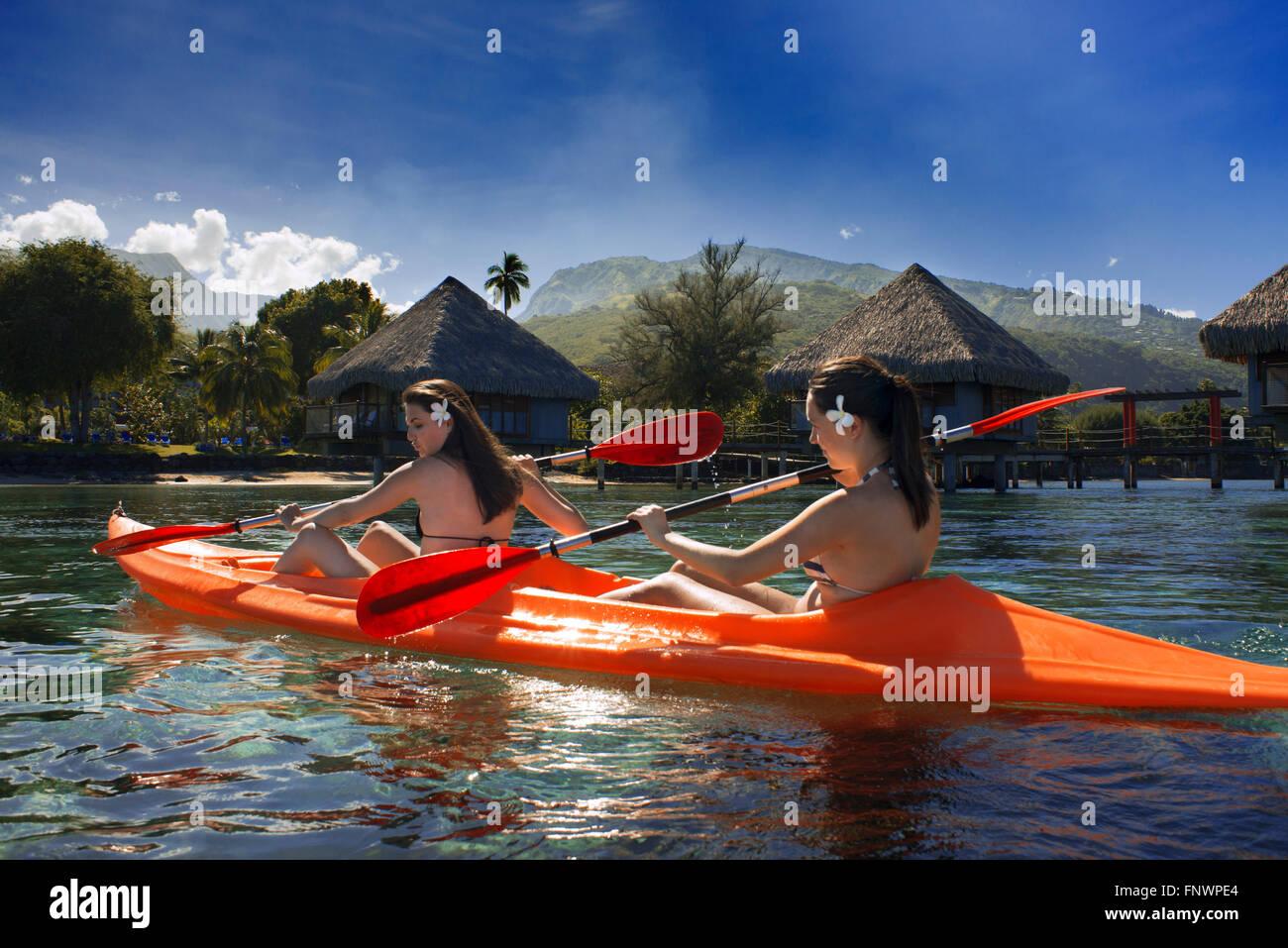 Deux belles filles faisant du kayak en face de Meridien Hotel sur l'île de Tahiti, Polynésie Française, Photo Stock