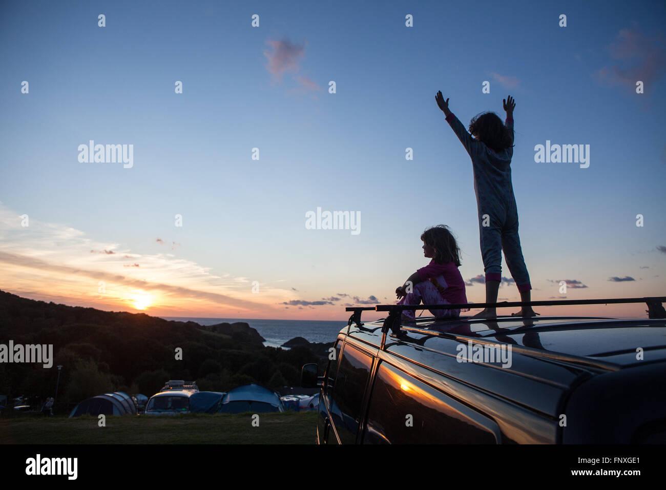 Deux jeunes enfants regarder le coucher du soleil sur un camping. Les souvenirs d'enfance sont faites sur des Photo Stock