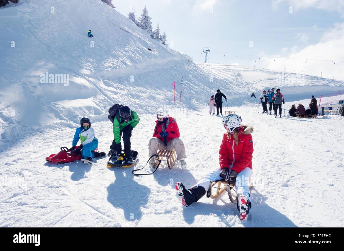 Les adolescents et les enfants de la luge dans les Alpes suisses à Lenk, Canton de Berne, Suisse, Europe Photo Stock