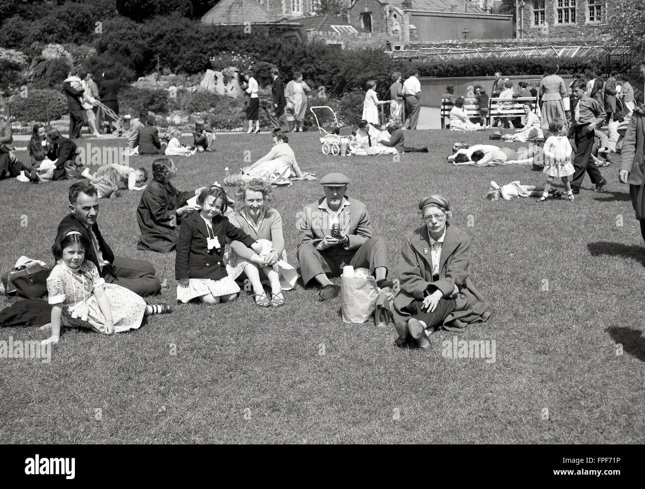 Historique années 1950, family sitting on grass à l'extérieur de maison historique. Photo Stock