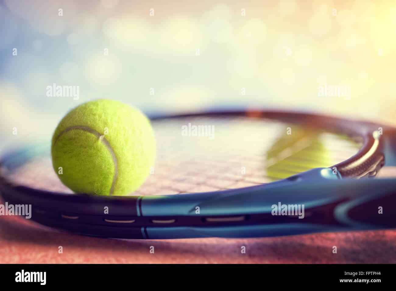 Balle de tennis reposant sur une raquette de tennis sur un cour d'asphalte rouge Photo Stock