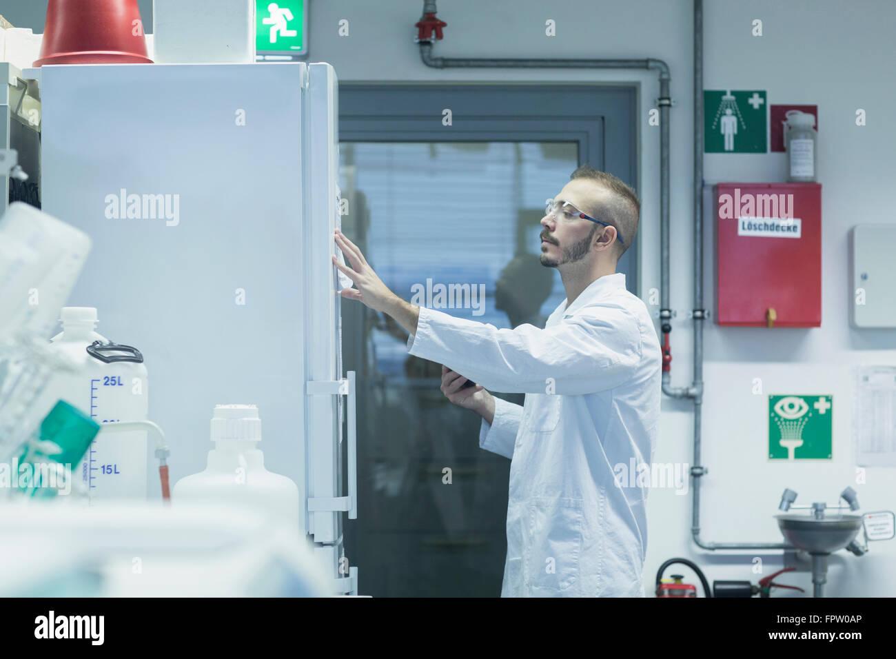 Jeune homme notes de lecture scientifique dans un laboratoire de pharmacie, Freiburg im Breisgau, Bade-Wurtemberg, Photo Stock