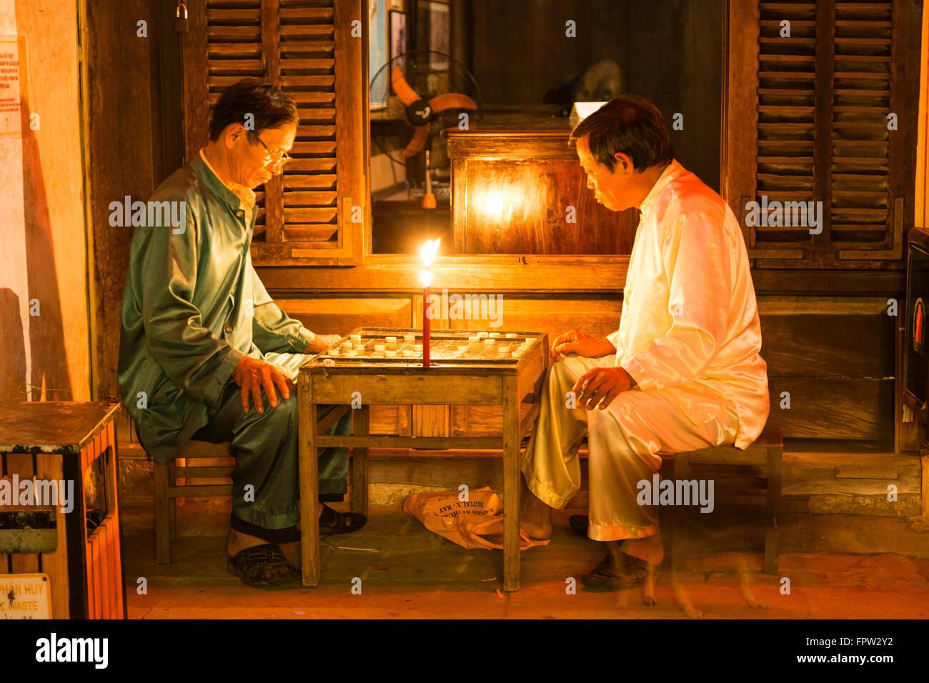 Les hommes jouant à la lumière d'une bougie d'un jeu, de la vieille ville de Hoi An, Vietnam Banque D'Images