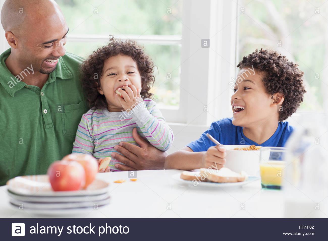 Père ayant un rire avec fils pendant le petit déjeuner Photo Stock