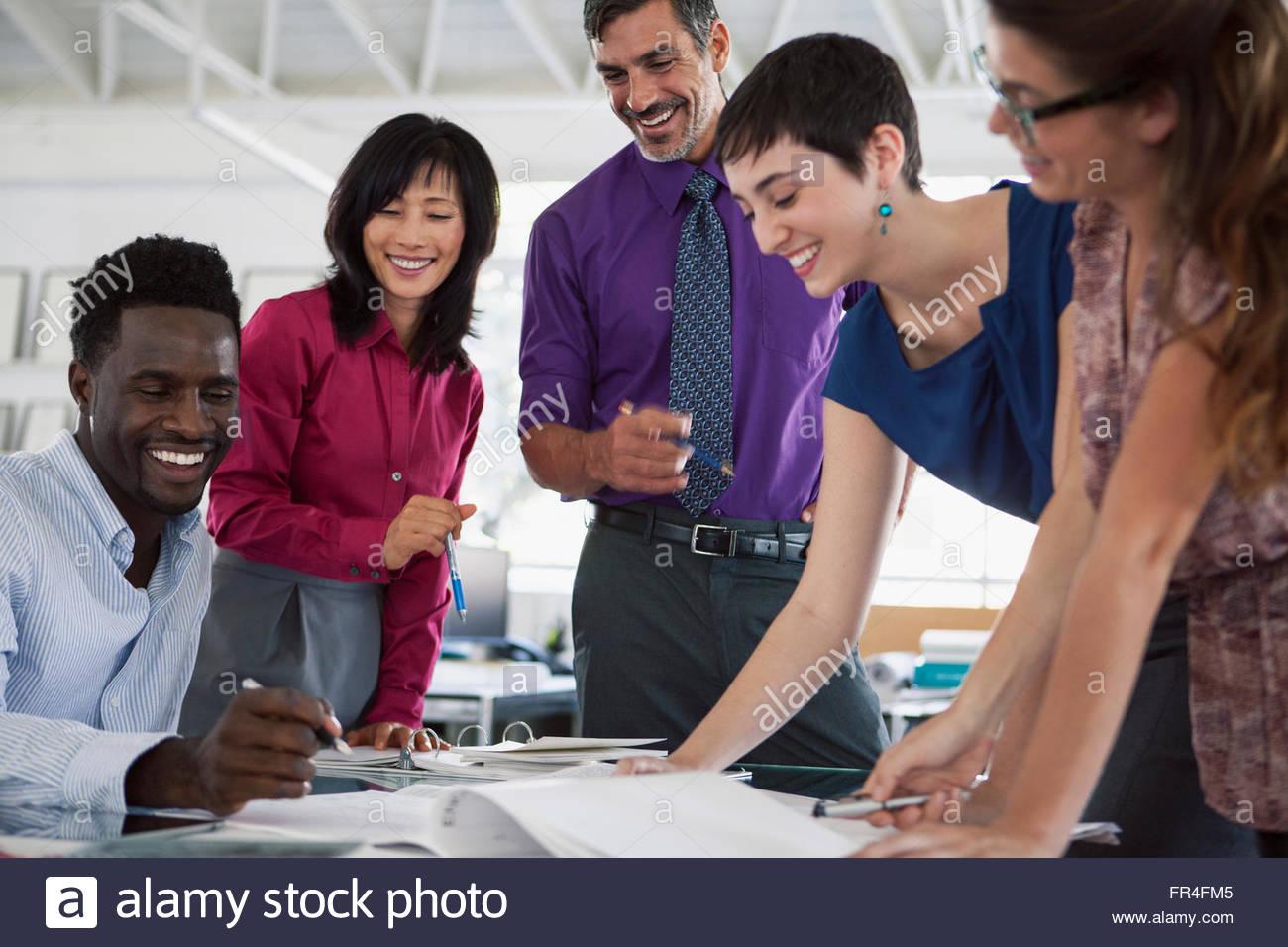 Les gens d'affaires ayant un rire alors que l'examen des formalités administratives Photo Stock