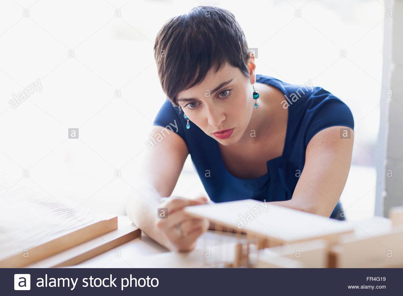 Jeune femme élégante à la recherche à architectural model Photo Stock