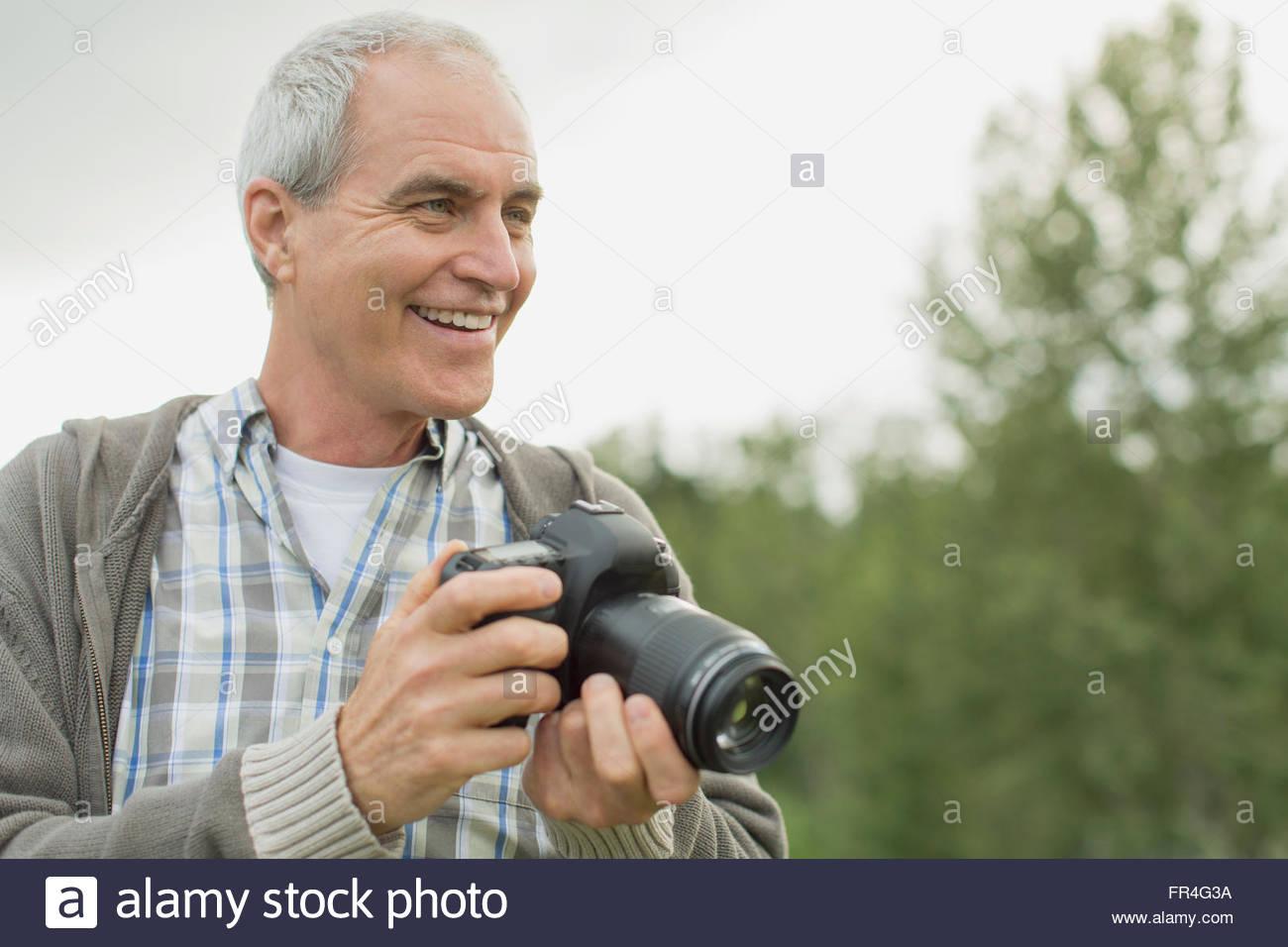 Middle-aged man smiling pendant le tournage avec caméra. Photo Stock