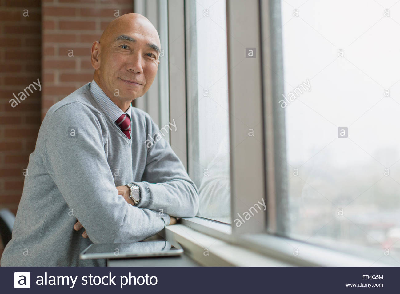 Portrait of senior Asian businessman à fenêtre. Photo Stock