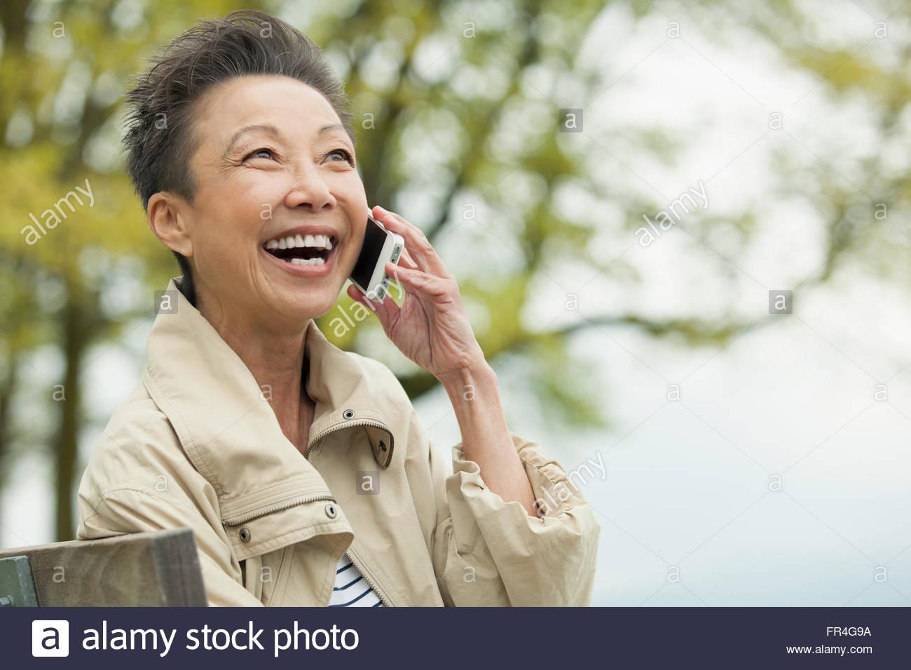 Femme Asiatique d'âge moyen ayant un rire tandis que sur la cellule Photo Stock