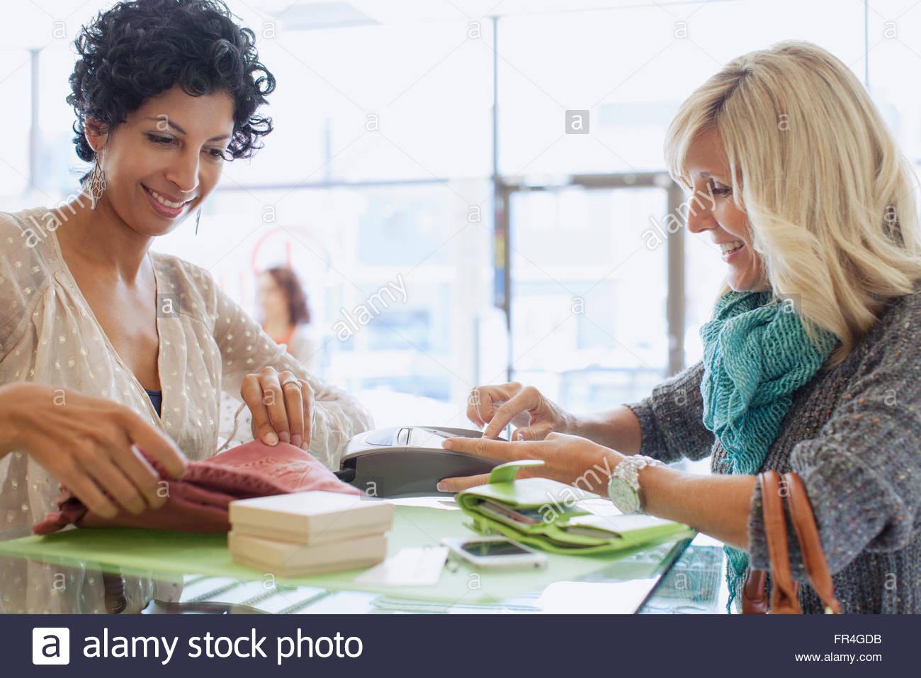 Femme à l'aide de carte de débit pour payer à l'achat. Photo Stock