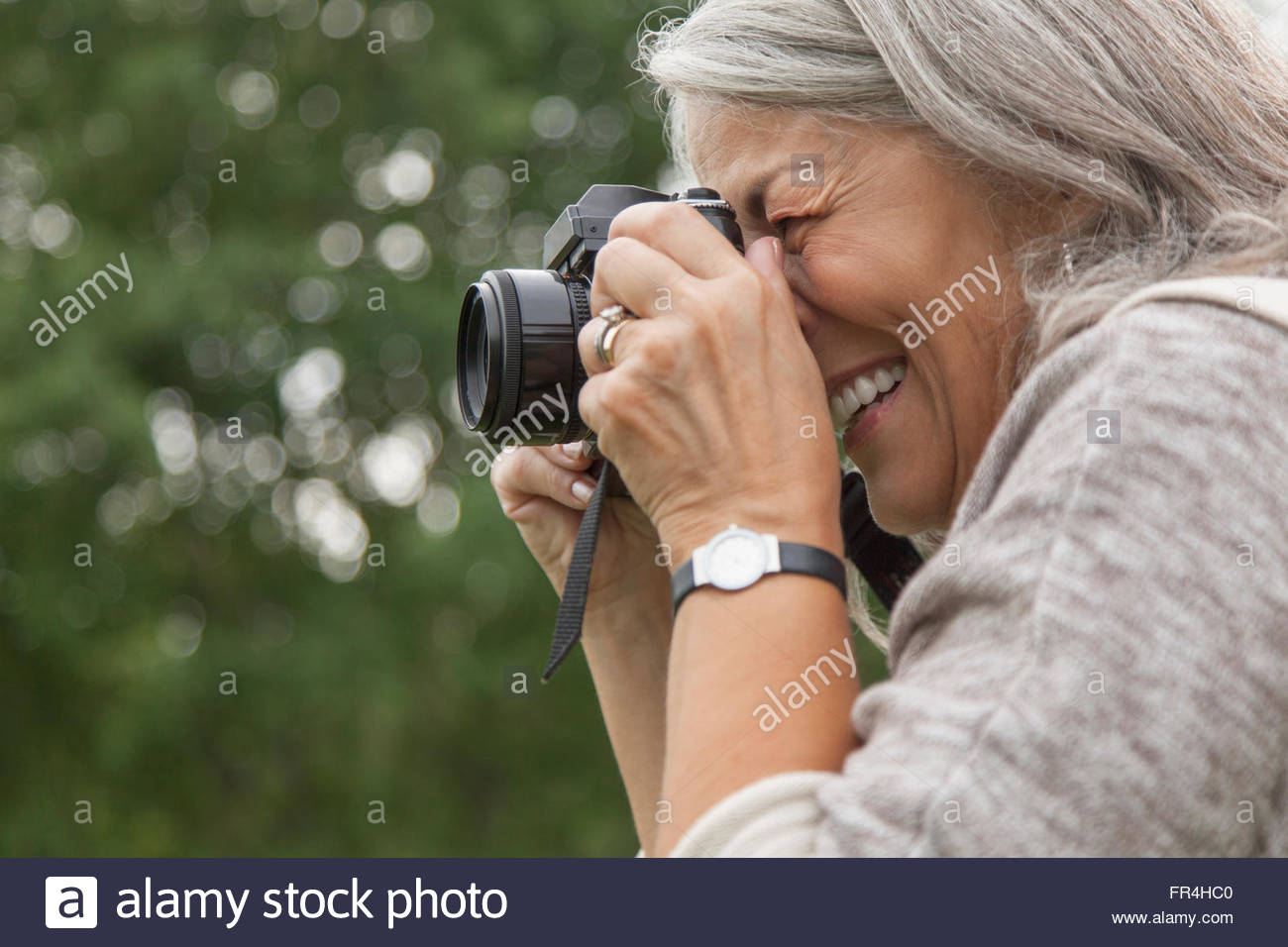 Senior woman taking pictures outdoors Photo Stock