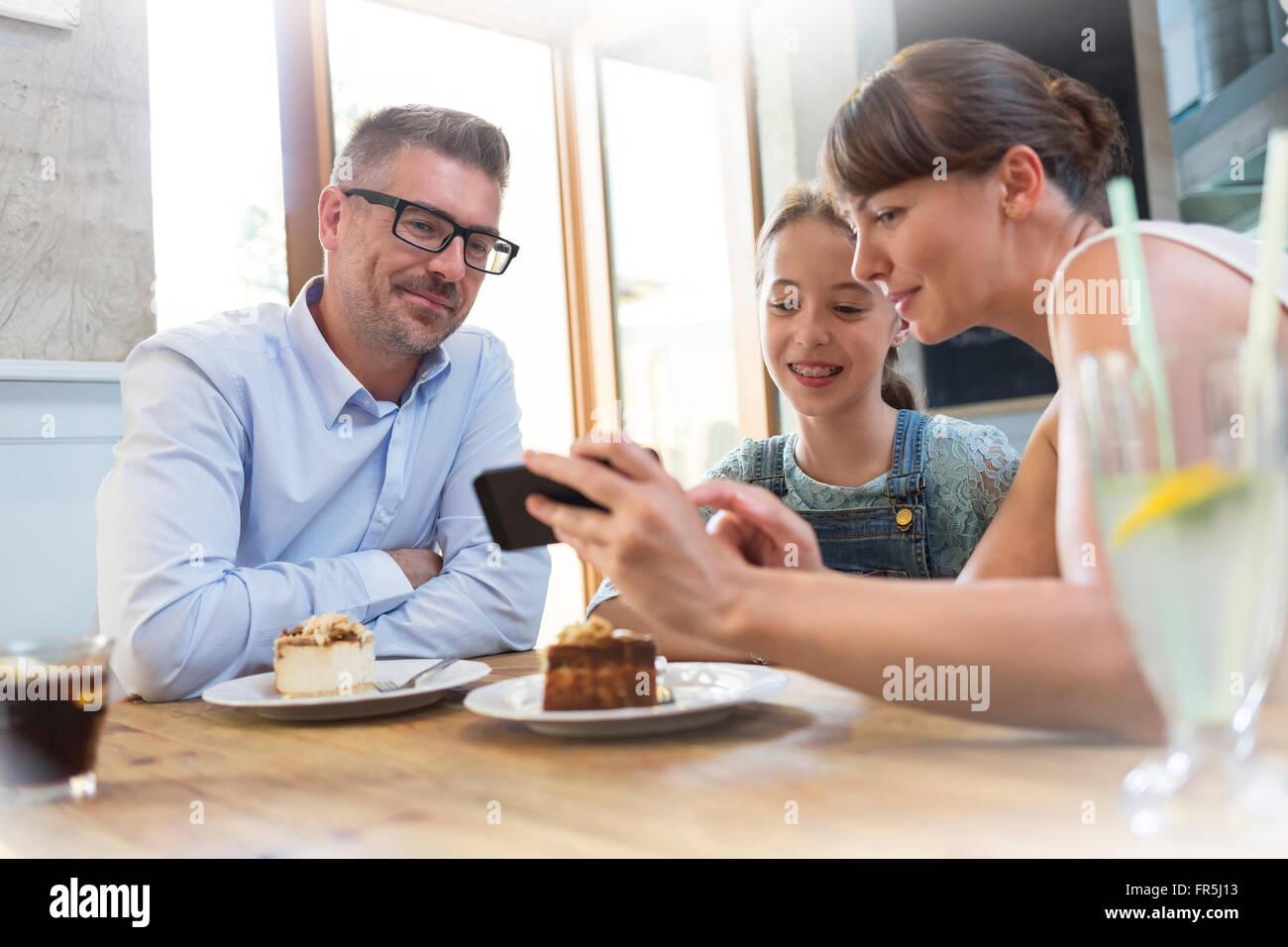 Famille avec cell phone manger dessert au cafe table Banque D'Images
